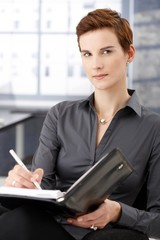 Portrait of businesswoman taking notes