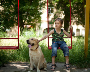 Little boy playing on a swing with dog