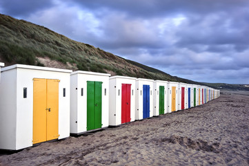 Row of colorful beach huts receding into distance on empty beach