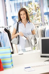 Happy woman paying in clothes store