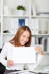 junge frau im büro zeigt weißes schild