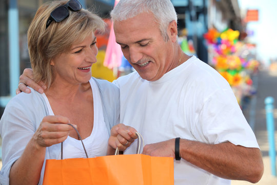 mature couple watching a carton bag