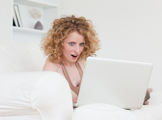 Lovely surprised female relaxing with her laptop while sitting o