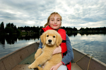 kid and a puppy in a boat on a lake