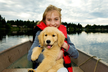 cute girl with a puppy on a boat