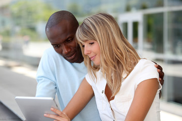 Couple using electronic tablet in town