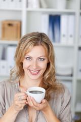 blonde frau genießt kaffee im büro