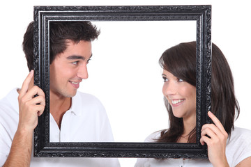 Young couple behind photo frame