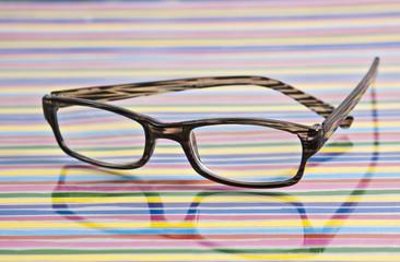 liegende Brille auf Untergund mit bunten Streifen