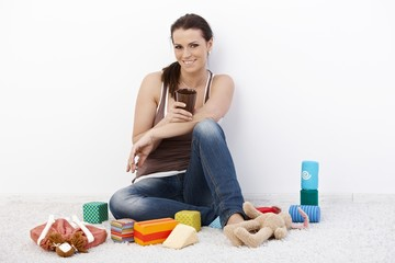 Smiling woman surrounded by baby toys
