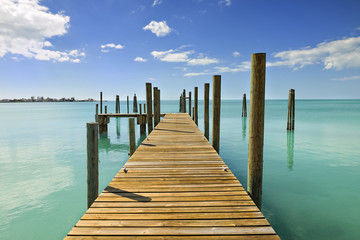 Keuken foto achterwand Pier Mooring posts and pontoon leading in turquoise blue sea