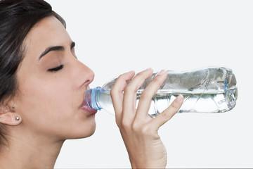 Mujer joven bebiendo agua ojos cerrados