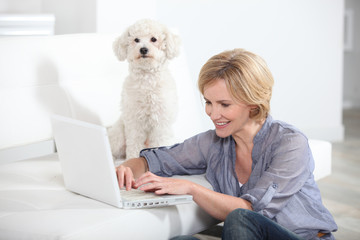 Woman using laptop computer next to small white dog