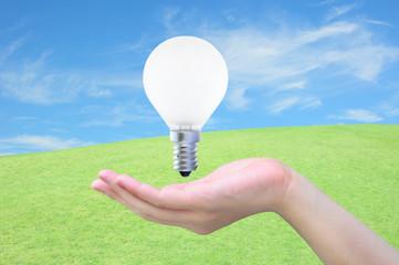 light bulb in women hand on sky