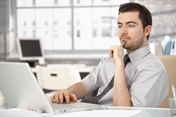 Young male sitting at desk working on laptop