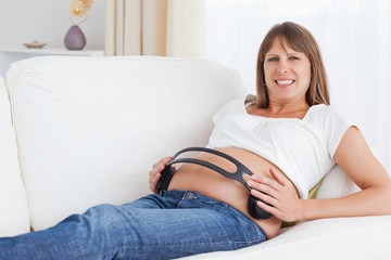 Smiling pregnant woman with headphones on her belly