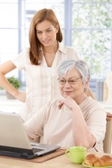 Grandmother browsing internet with granddaughter