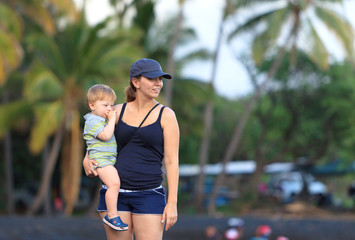 Young mother holding her son at a Hawaiian black sand beach