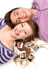 Young couple lying down with polaroid pictures