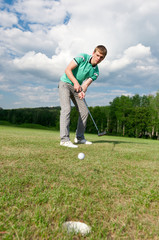 Golf green hole course man putting ball inside short putt