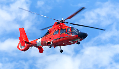 Foto auf Acrylglas Hubschrauber Red rescue helicopter moving in blue sky