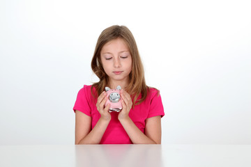 Portrait of young girl holding piggy bank