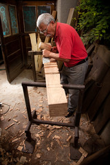 woodcarver working with mallet and chisel