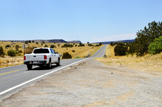 View of long highway with white pickup truck in foreground