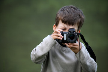 Cute little caucasian boy taking photos