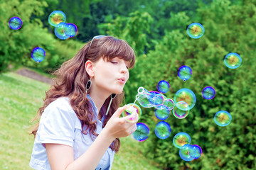 attractive girl inflating colorful soap bubbles in spring park
