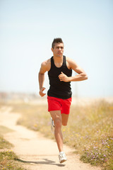 healthy young man running on a mountain road