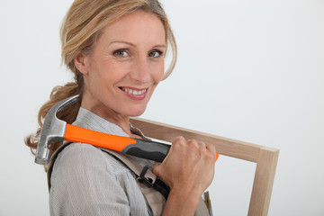 Woman with a picture frame and hammer.