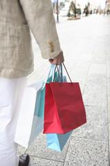 ショッピングバッグを持つ男性の手元
