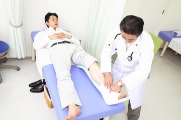 患者の足に包帯を巻く医者