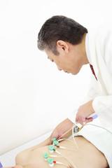 心電図の吸盤を男性患者に取り付ける医者