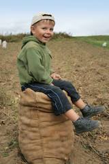 smiling boy sitting on a sack of potatoes