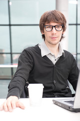Friendly executive sitting in front of laptop
