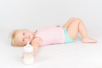Adorable baby lie on white floor, rest after eating milk from th