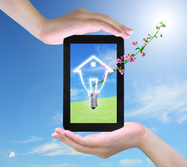 light bulb model of a house and pink flower on tablet PC