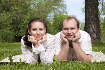 couple lays together on a grass