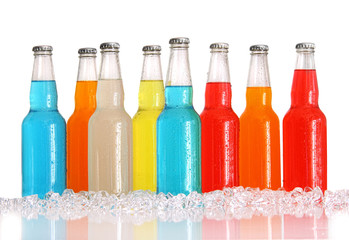 Bottles of multi-color drinks with ice on white