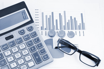 Coins, glasses and calculator on paper table with diagram