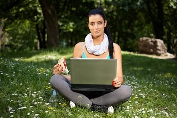 Beautiful woman using laptop in park