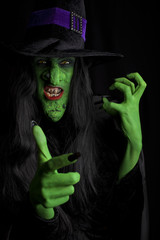Angry green witch, black background.