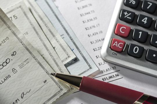 Checks, calculator, statement and pen