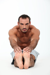 Fit man touching his toes