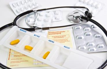 Krankmeldung  mit Tabletten und Stethoskop