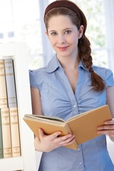 Attractive young woman reading at home smiling