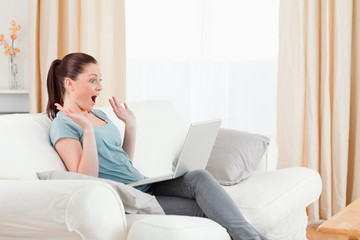 Joyful woman gambling with her computer while sitting on a sofa