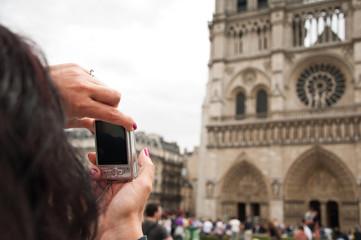 femme brune prenant notre dame en photo